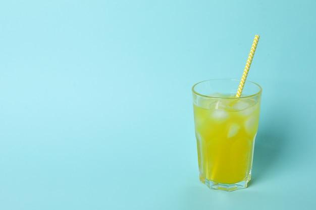 Copo de refrigerante de laranja com cubos de gelo e canudo na superfície azul