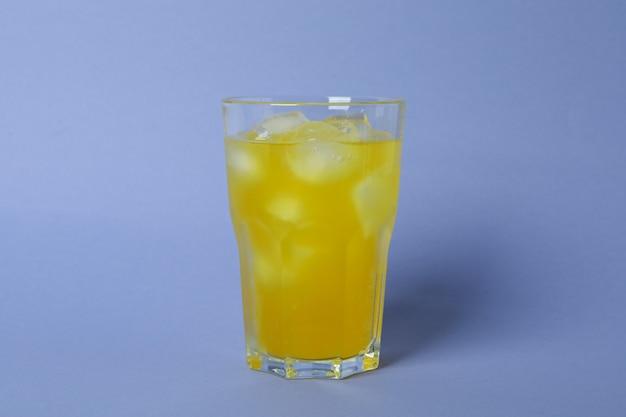 Copo de refrigerante de laranja com cubos de gelo na superfície violeta