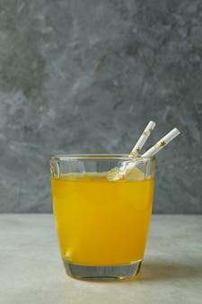 Copo de refrigerante de laranja na mesa texturizada branca contra a superfície cinza