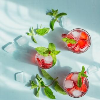 Copo de refrigerante de morango beber em azul claro. limonada desintoxicante saudável de verão, coquetel ou outra bebida