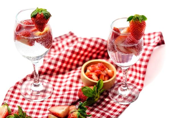 Copo de refrigerante de morango colocado sobre uma toalha de mesa xadrez isolada no branco.