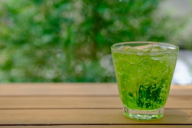 Copo de refrigerante verde gelado na mesa de madeira com jardim natureza