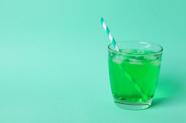 Copo de refrigerante verde na superfície de hortelã