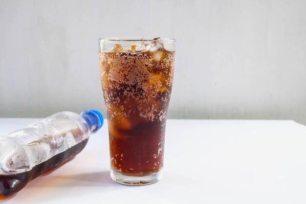 Copo de refrigerantes e refrigerantes pretos na mesa