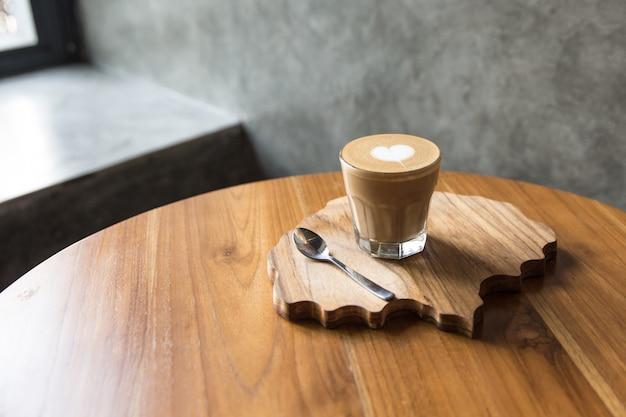 Copo de saboroso último com arte de amor na mesa de madeira e mesa texturizada.