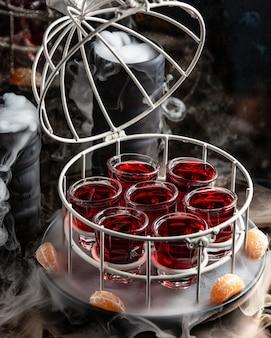 Copo de shot vermelho servido em gaiola com tampa aberta em panela defumada