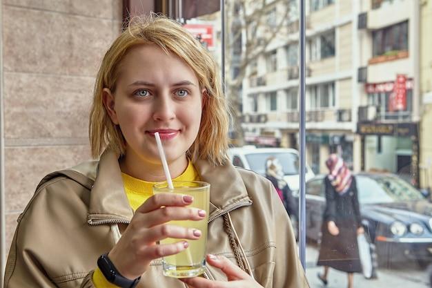 Copo de suco com canudo nas mãos de uma bela jovem caucasiana sentada perto da janela dentro de um café com vista para a rua.