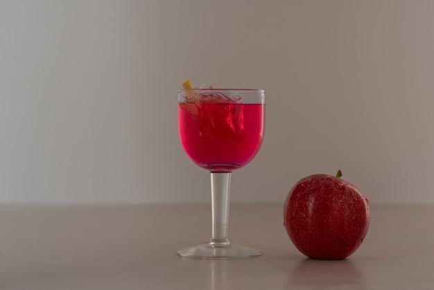 Copo de suco com maçã vermelha.