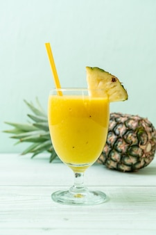 Copo de suco de abacaxi fresco na mesa de madeira - bebida saudável