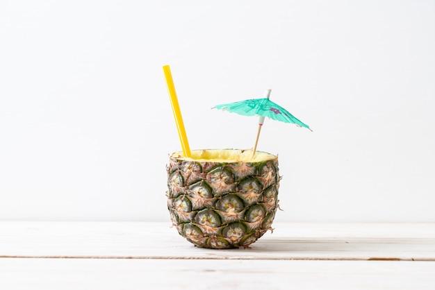 Copo de suco de abacaxi fresco na mesa de madeira