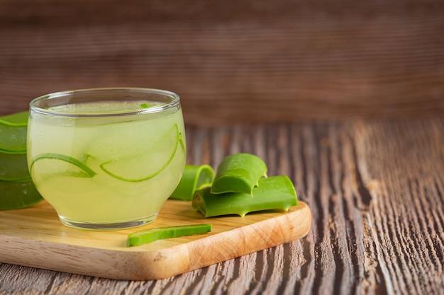 Copo de suco de aloe vera colocado em uma tábua de madeira