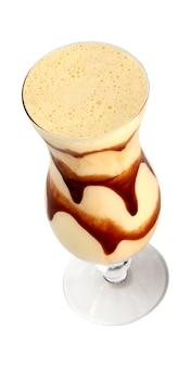 Copo de suco de frutas com calda de chocolate na superfície branca
