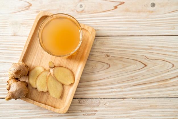Copo de suco de gengibre fresco e quente com raízes de gengibre - estilo de bebida saudável