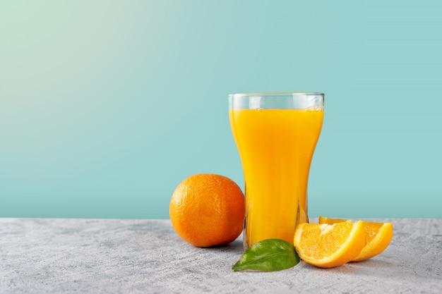 Copo de suco de laranja com laranjas na parede azul claro