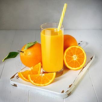 Copo de suco de laranja e frutas frescas em uma mesa de madeira branca, estilo vintage