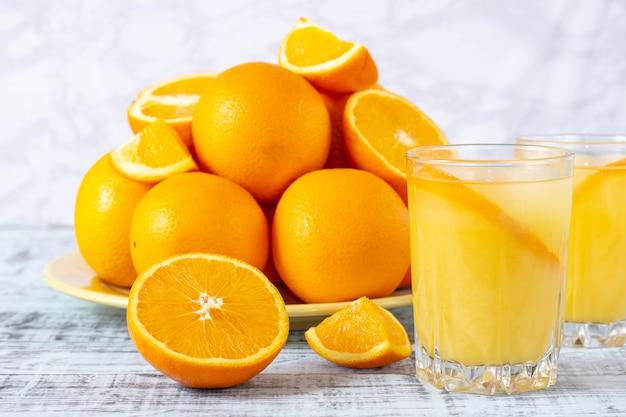 Copo de suco de laranja e um prato com laranjas em uma mesa de madeira. suco de laranja espremido na hora.