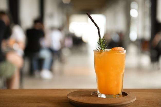 Copo de suco de laranja em uma bandeja de madeira, colocada sobre uma mesa no café turva fundo.