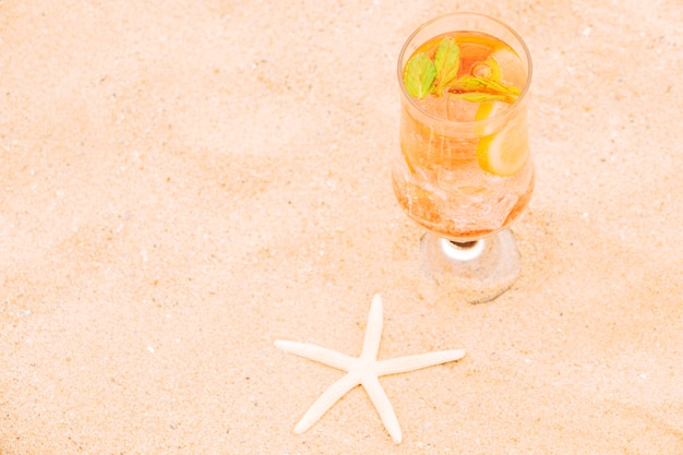 Copo de suco de laranja fresco com fatias de frutas cítricas e estrelas do mar
