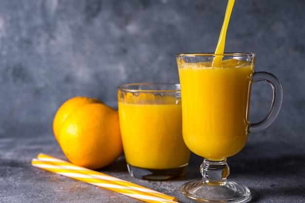 Copo de suco de laranja fresco, frutas maduras e fatias de laranja