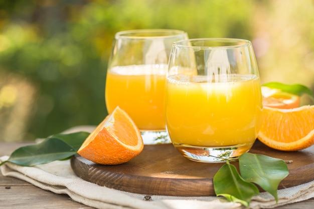 Copo de suco de laranja fresco, frutas maduras e fatias em natural. suco de laranja espremido com canudo, frutas e fatias de laranja.
