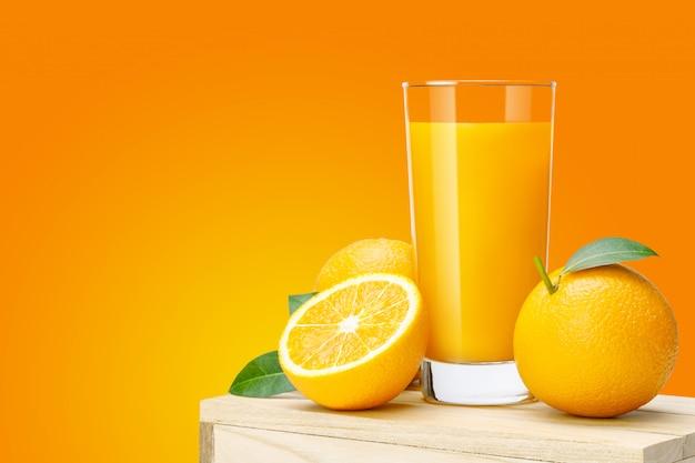Copo de suco de laranja fresco na caixa de madeira, suco de laranja de frutas frescas em vidro com grupo sobre fundo de cor laranja com espaço de cópia para o seu texto.