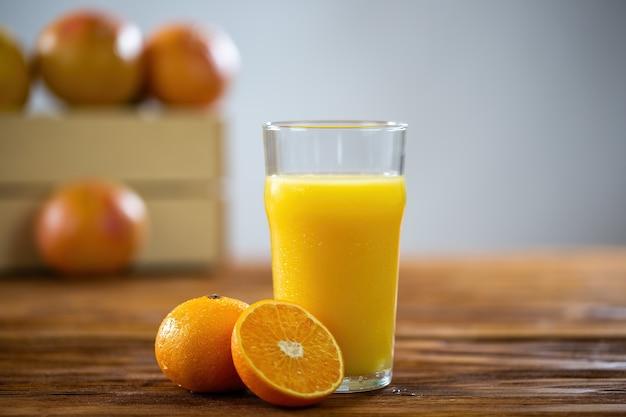 Copo de suco de laranja fresco na mesa de madeira com toranjas no fundo