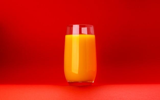 Copo de suco de laranja isolado em fundo vermelho