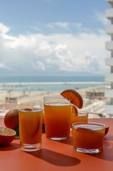 Copo de suco de laranja na mesa com vista para o mar