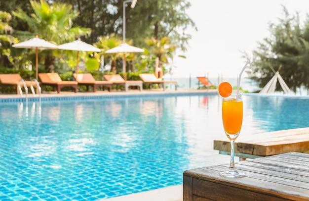 Copo de suco de laranja na mesa de madeira com vista para a piscina