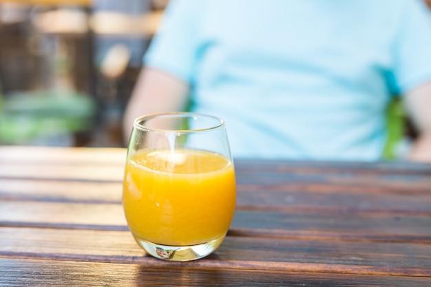 Copo de suco de laranja na mesa de madeira no café da rua