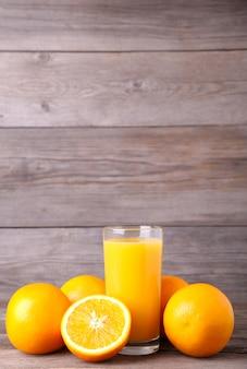 Copo de suco de laranja na mesa de madeira