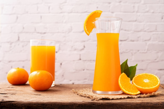 Copo de suco de laranja na mesa de madeira.