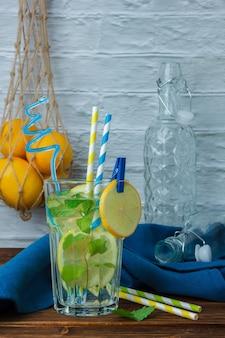 Copo de suco de limão com caixa de madeira e limões e vista lateral de pano azul em uma superfície de madeira e branca