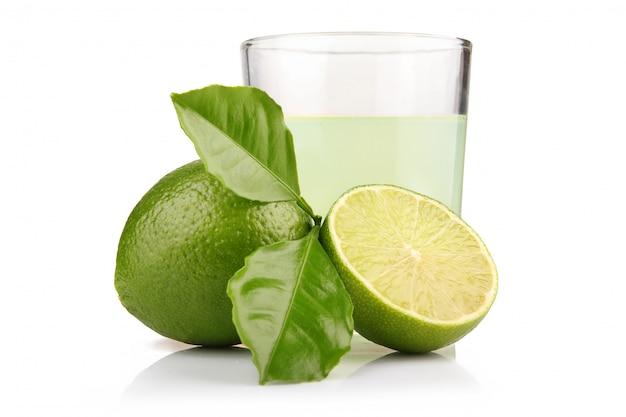 Copo de suco de limão e limão frutas com folhas verdes isoladas