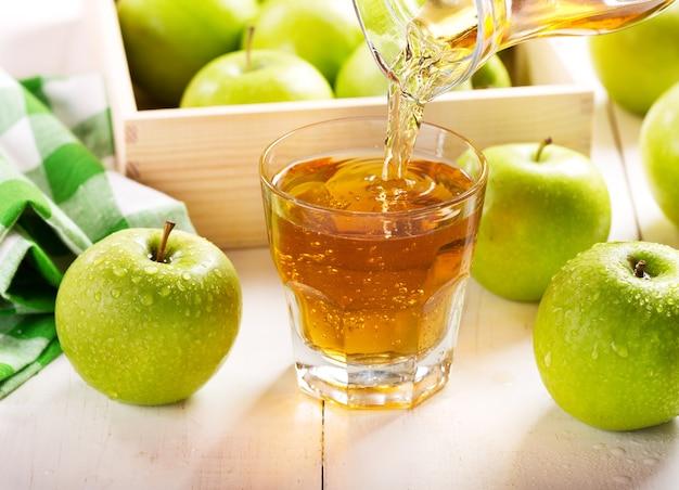 Copo de suco de maçã com frutas frescas na mesa de madeira