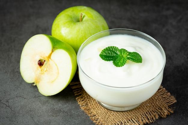 Copo de suco de maçã verde saudável colocado ao lado de maçãs verdes frescas