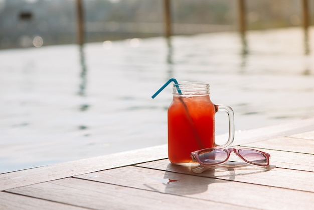 Copo de suco de melancia batido na beira de uma piscina - conceito tropical de férias