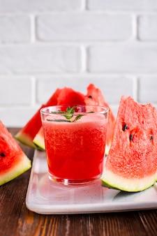 Copo de suco de melancia close-up no prato