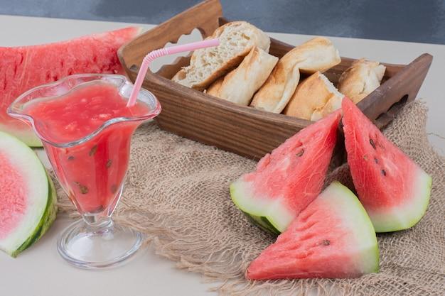 Copo de suco de melancia e cesta de pão na mesa branca.