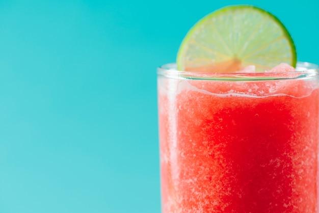 Copo de suco de melancia saudável no verão sobre fundo azul.