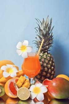 Copo de suco de multifrutas exóticas tropicais cocktail com flores de frangipani e frutas no fundo