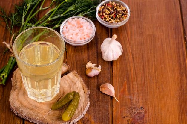 Copo de suco de pickle, pepino em conserva na madeira