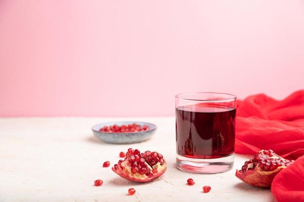 Copo de suco de romã em um fundo branco e rosa com tecido vermelho.