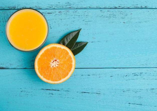 Copo de suco de suco de laranja orgânico fresco com laranja crua sobre fundo azul de madeira.