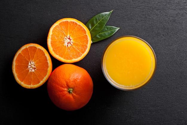 Copo de suco de suco de laranja orgânico fresco com laranjas cruas em fundo preto de madeira.
