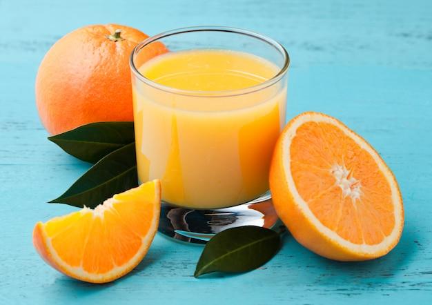 Copo de suco de suco de laranja orgânico fresco com laranjas cruas sobre fundo azul de madeira.