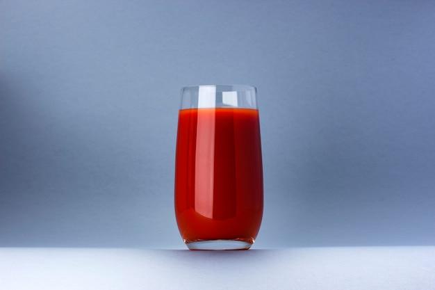 Copo de suco de tomate isolado no fundo branco, com espaço de cópia