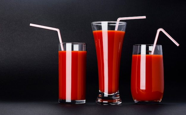 Copo de suco de tomate isolado no preto, com espaço de cópia