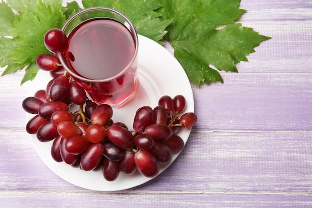Copo de suco de uva na mesa de madeira, closeup