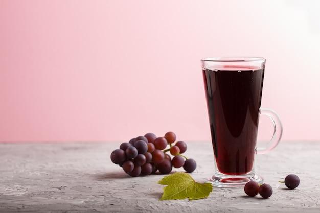 Copo de suco de uva vermelha em um fundo cinza e rosa. vista lateral